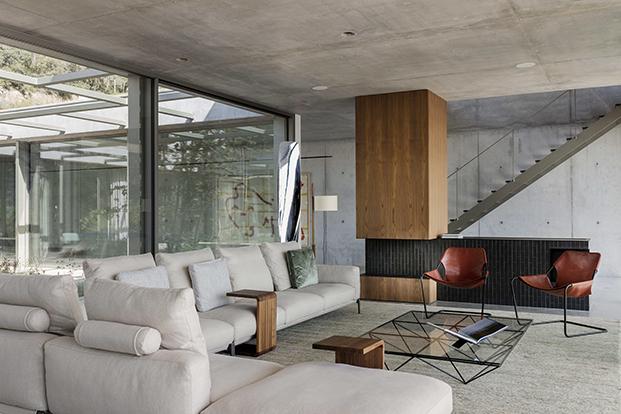 Vista del salón abierto al patio y la escalera volada que conduce a la planta alta. El sofá es de Flexform las butacas de SIllón Paulistano de Paulo Mendes Da Rocha para Objekto