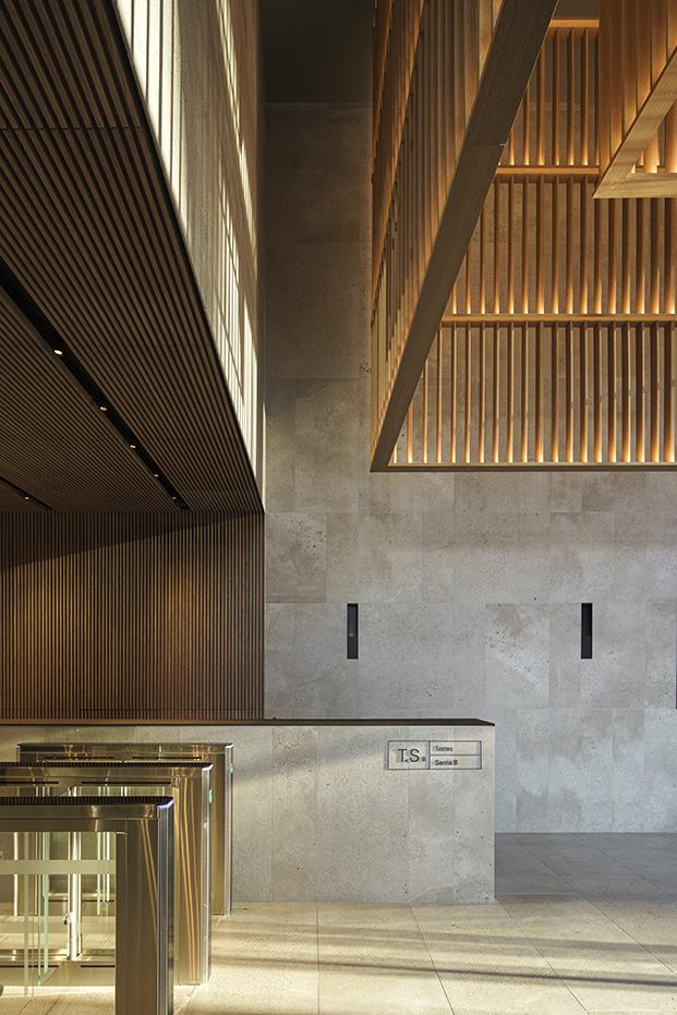 La madera iluminada con la luz del atardecer contrasta con la piedra gris que envuelve el edificio