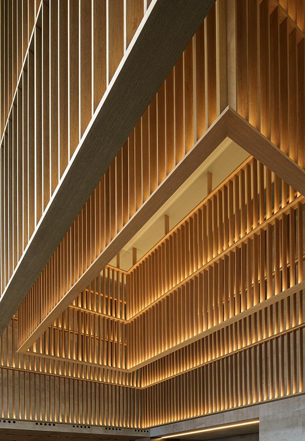 Listones de madera, tanto en vertical como en horizontal reflejan la luz en contraste con la piedra gris