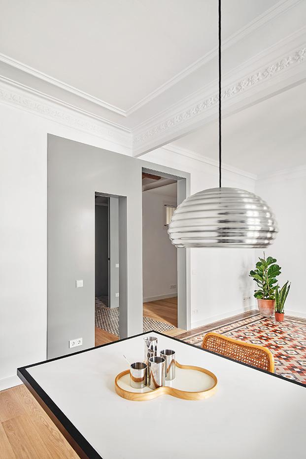 Una mesa de comedor y trabajo conecta la zona de estar y salón con la de la cocina