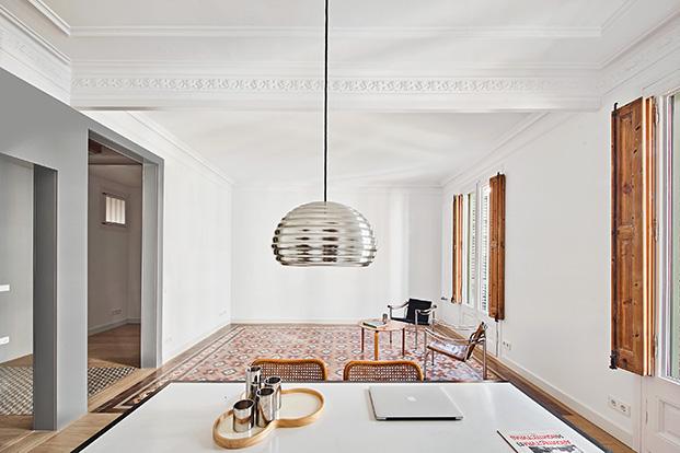 Vista desde la mesa de la cocina de la zona de estar del salón de la vivienda rehabilitada del Eixample aún sin terminar decorar